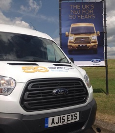 The Manheim Transit 50th van posing with a Ford Transit 50th poster
