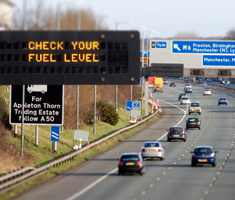 Motorway with sign saying to check your fuel level