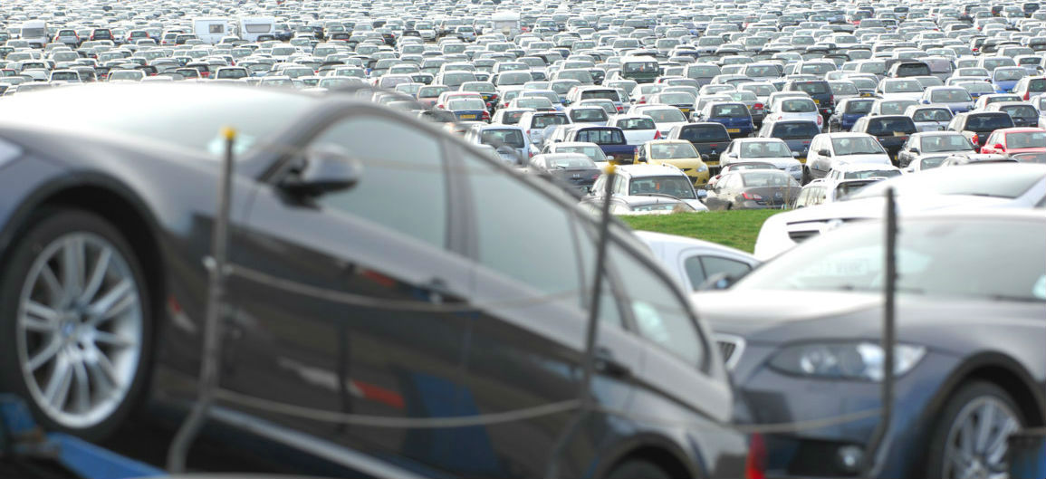 Cars on a transporter near a busy auction centre car lot