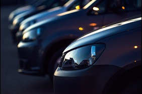A line up of car at a dealership at night